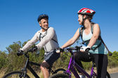 Active couple going for a bike ride in the countryside — Stock Photo