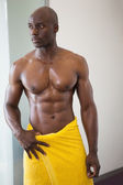 Muscular man wrapped in yellow towel — Stok fotoğraf