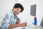 Young designer working at his desk smiling at camera — Stock Photo