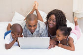 Happy family using laptop together on bed — Stock fotografie