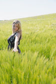 Pretty blonde in sundress standing in wheat field — Stock Photo