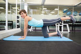 Fit brunette souriante faire pilates sur tapis d'exercice — Photo