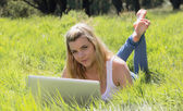 Pretty blonde lying on grass using laptop smiling at camera — Stock Photo