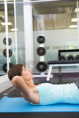 Fit brunette doing sit up on exercise mat — Stok fotoğraf