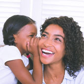 Pretty mother sitting on the couch with her daughter whispering  — Stock Photo