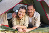 Outdoorsy couple smiling at camera from inside their tent — 图库照片