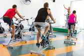 Spin class working out with motivational instructor — Stock Photo