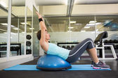 Fit brunette using bosu ball to work out — Stock Photo