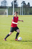 Football player in red playing on pitch — Stockfoto