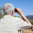 Hiker taking a break on country trail looking through binoculars — Stock Photo #50050317