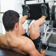Male weightlifter doing leg presses in gym — Stock Photo #50050835