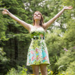 Woman with arms outstretched in field against trees — Stock Photo #50050843