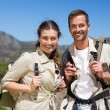 Hiking couple standing and smiling at camera on country terrain — Stock Photo #50050873