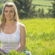 Pretty blonde smiling at camera sitting on grass — Stock Photo #50051055