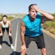 Fit couple jogging on the open road together — Stock Photo #50051125