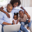 Happy family sitting on couch together using laptop — Stock Photo #50051425