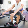 Fit smiling brunette working out on rowing machine — Stock Photo #50051589