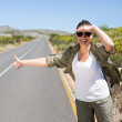 Pretty hitchhiker sticking thumb out on the road — Stock Photo #50051607