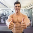 Smiling muscular man giving thumbs up in gym — Stock Photo #50052027