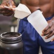 Body builder holding a scoop of protein mix — Stock Photo #50052235