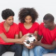 Football fans sitting on couch holding ball — Stock Photo #50052949