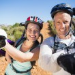 Active couple carrying their bikes on country terrain together — Stock Photo #50053297