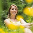 Cute young woman relaxing in field — Stock Photo #50053435