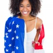 Pretty girl wrapped in american flag smiling at camera — Stock Photo #50053469