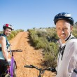 Active couple cycling on country terrain together — Stock Photo #50053545