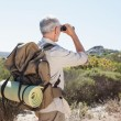 Hiker looking through binoculars on country trail — Stock Photo #50053829