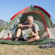 Happy camper looking at map sitting in his tent — Stock Photo #50053901
