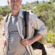 Handsome hiker smiling at camera in the countryside — Stock Photo #50053971