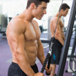 Shirtless muscular man using triceps pull down in gym — Stock Photo #50054009