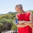 Fit man changing the song on his music player on mountain trail — Stock Photo #50054127