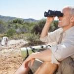 Hiker taking a break on country trail looking through binoculars — Stock Photo