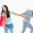 Attractive young man pulling his shopaholic girlfriend — Stock Photo #50054737