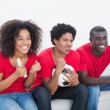 Football fans in red sitting on couch cheering — Stock Photo