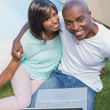 Happy couple sitting in garden using laptop together — Stock Photo #50054813