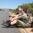 Hiking couple sitting on the side of the road — Stock Photo #50055205