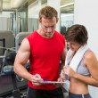 Handsome personal trainer with his client looking at clipboard — Stock Photo #50055529