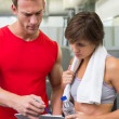 Handsome personal trainer with his client looking at clipboard — Stock Photo #50055539
