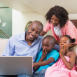 Happy family relaxing on the couch using laptop — Stock Photo #50055655