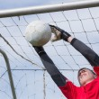 Goalkeeper in red jumping up to save a goal — Stock Photo