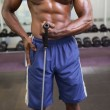 Muscular man using resistance band in gym — Stock Photo #50055833