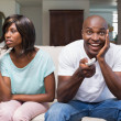 Woman sitting next to her boyfriend watching tv — Stock Photo #50055903