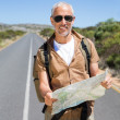 Handsome hiker holding map and smiling at camera — Stock Photo #50056371