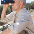 Hiker taking a break on country trail looking through binoculars — Stock Photo #50056405