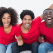 Football fans in red sitting on couch cheering — Stock Photo #50056411