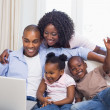 Happy family on the couch together using laptop — Stock Photo #50056933
