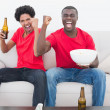 Football fans in red sitting on couch with beer and popcorn — Stock Photo #50057187